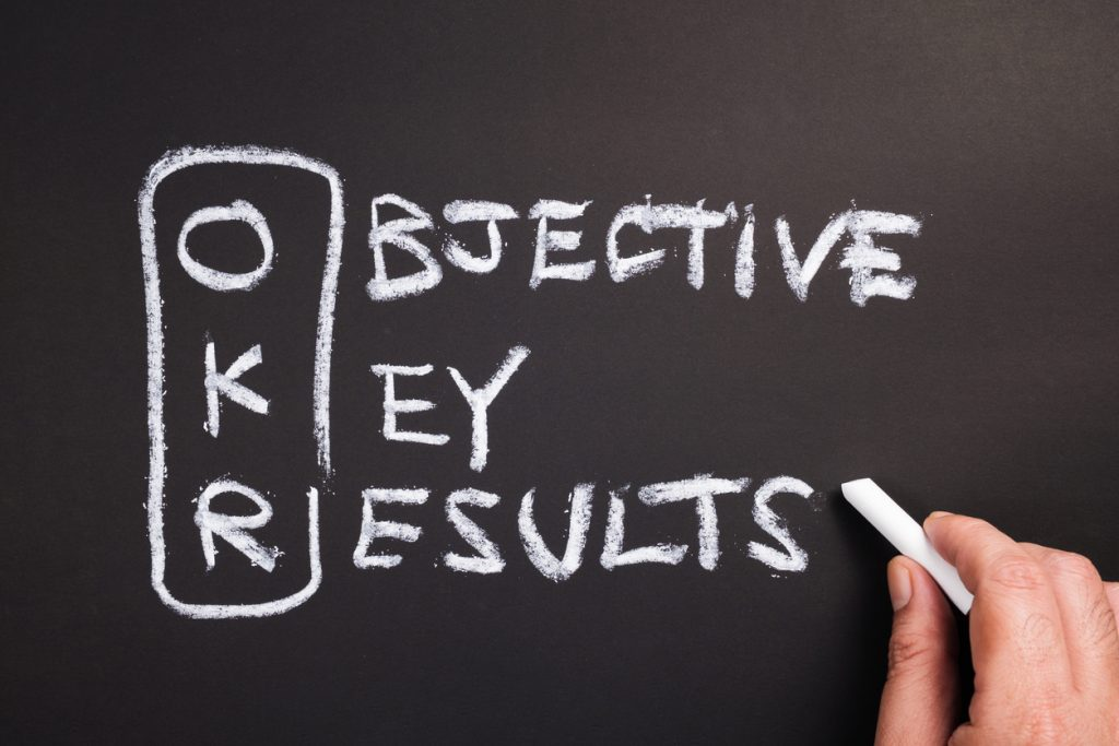 Hand writing text and acronym of OKR (Objective Key Results) on chalkboard. concept: OKR examples
