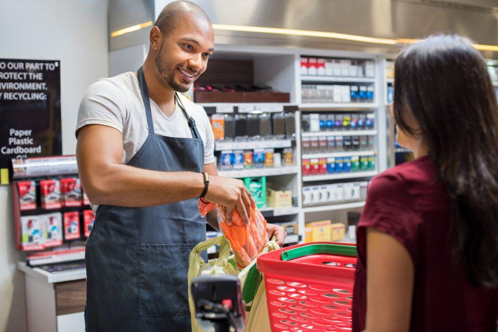 Dependiente en tienda atendiendo a cliente en caja. Concepto: aprecio por el cliente.