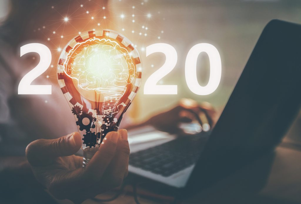 Número 2020 con mano y bombilla. Concepto: Mejor negocio para empezar en 2020