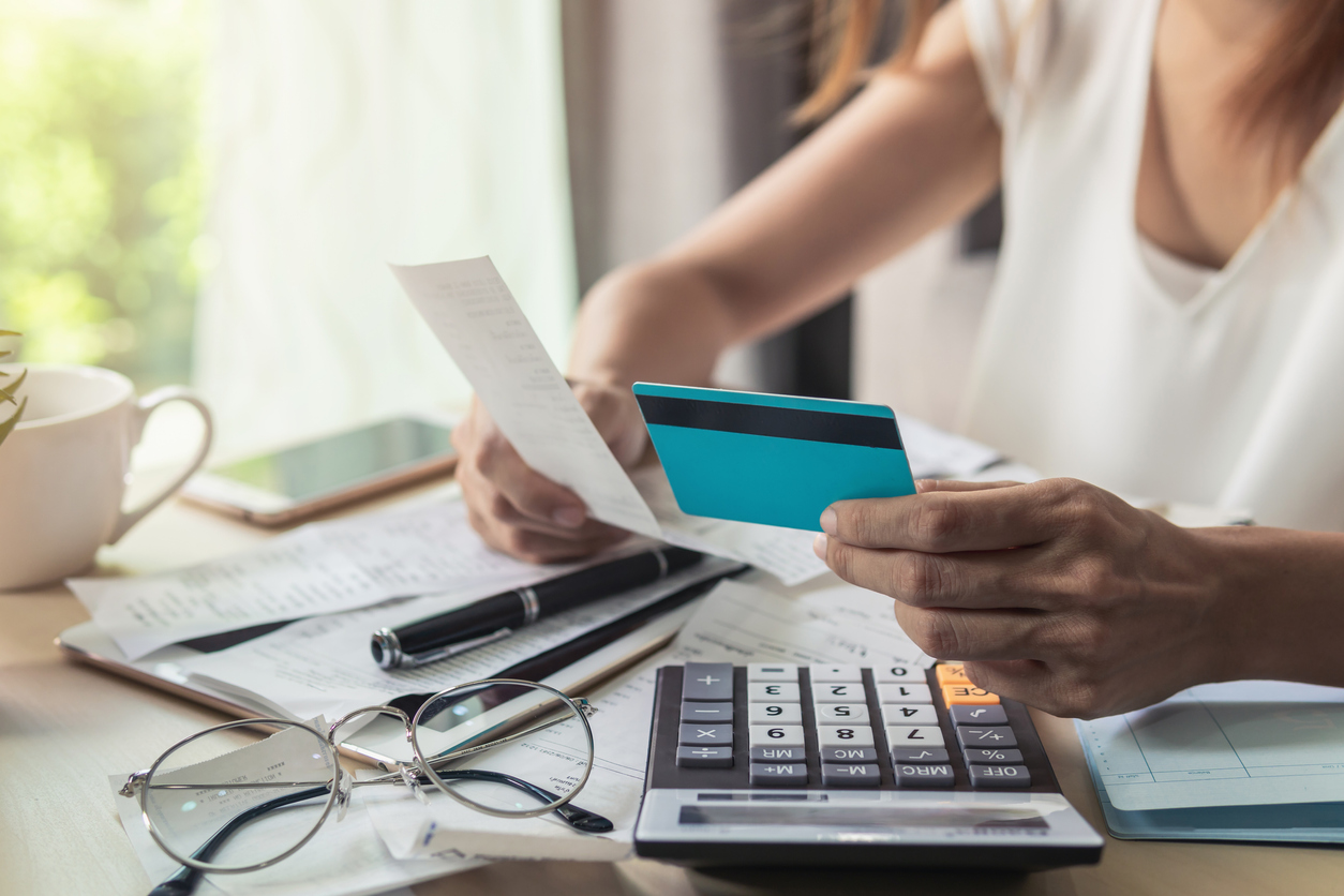 Young woman checking bills, taxes, bank account balance and calculating credit card expenses at home. concept: debt to credit ratio
