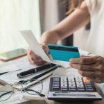 Mujer joven revisando su cuenta de banco, tarjeta de crédito, concept: relación deuda crédito