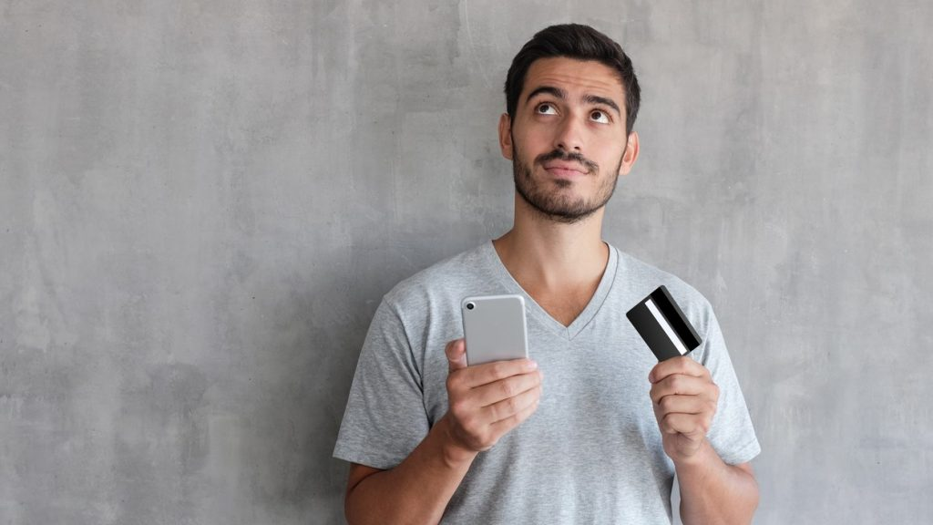 Young handsome man thinking about online shopping , wearing gray t shirt, standing against textured wall with copy space, holding credit card and cell phone. concept: sam's club business credit