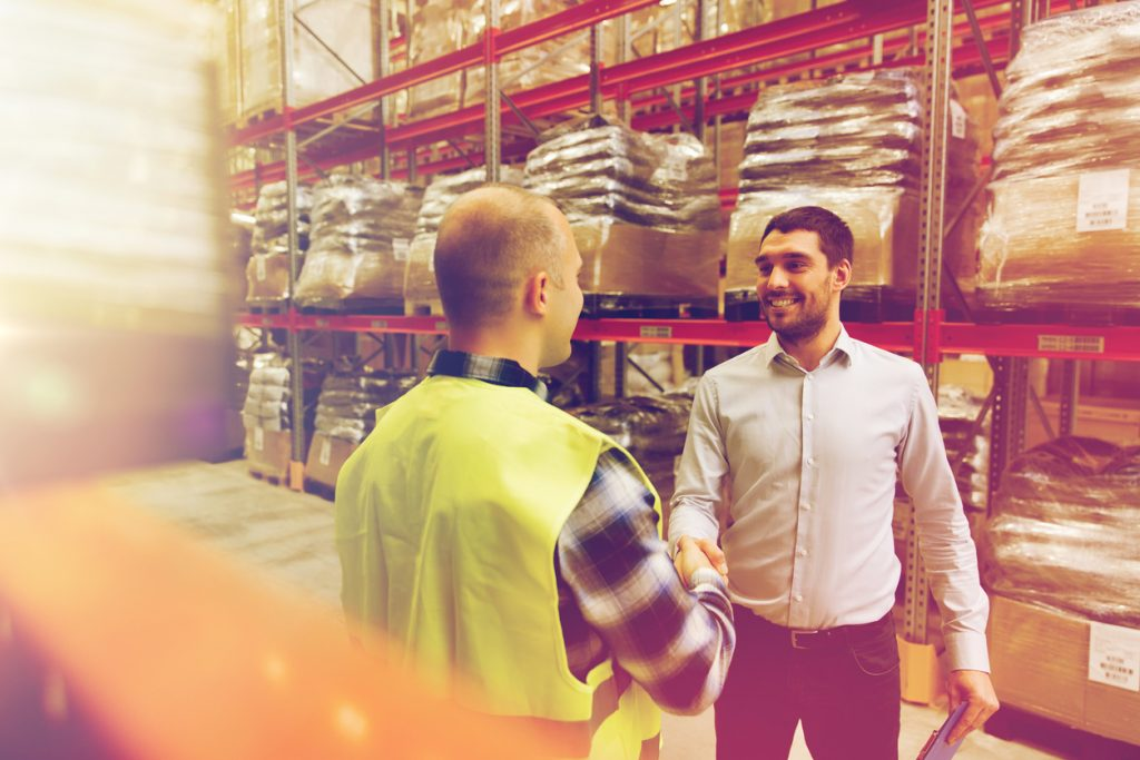 wholesale, logistic, people and export concept - manual worker and businessmen with clipboard shaking hands and making deal at warehouse. concept: trade credit