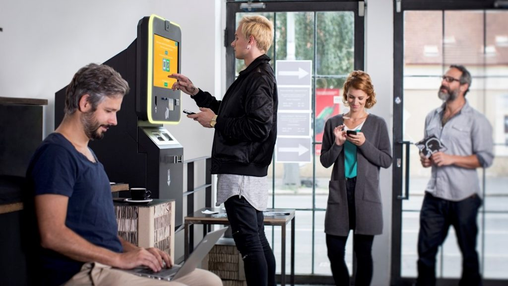People stand at BITCOIN ATM and buy the cryptocurrencies. concept: open a bank account online with no money
