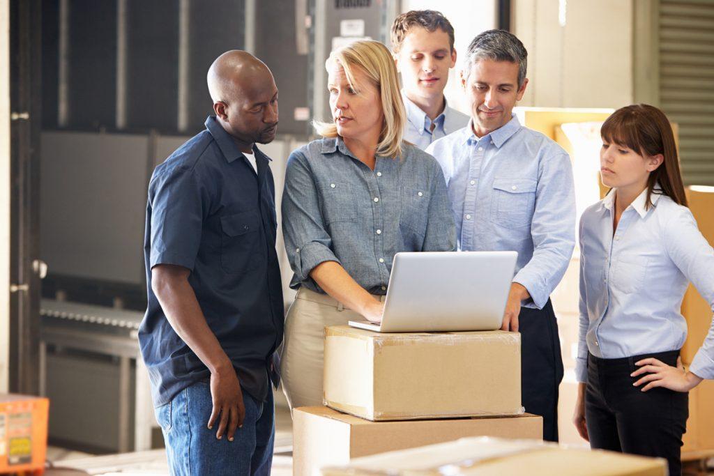 Grupo de trabajadores en almacén con laptop y hablando sobre el costo de los bienes vendidos