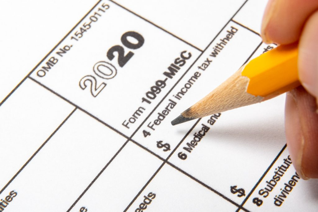 Primer plano del formulario 1099 y mano y lápiz.