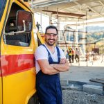 Worker leaning on company's truck and smiling to camera. Concept: Best auto loans for small businesses