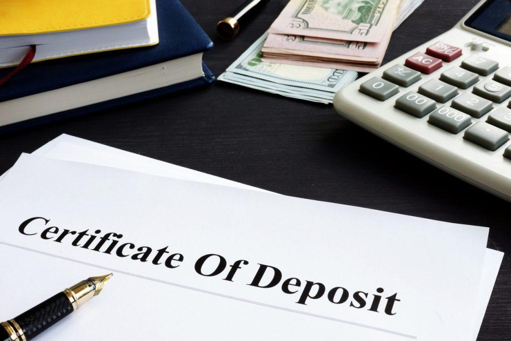 Certificado de depósito sobre escritorio junto a pluma, calculadora y dinero.