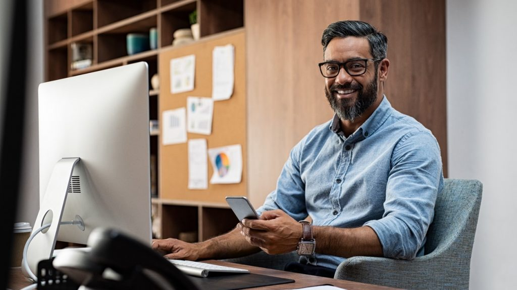 Smiling business man wearing eyeglasses working on desktop computer while using phone in office. Middle eastern businessman using smartphone while sitting at desk in office designer. Man working in modern business environment. concept: SBA grants