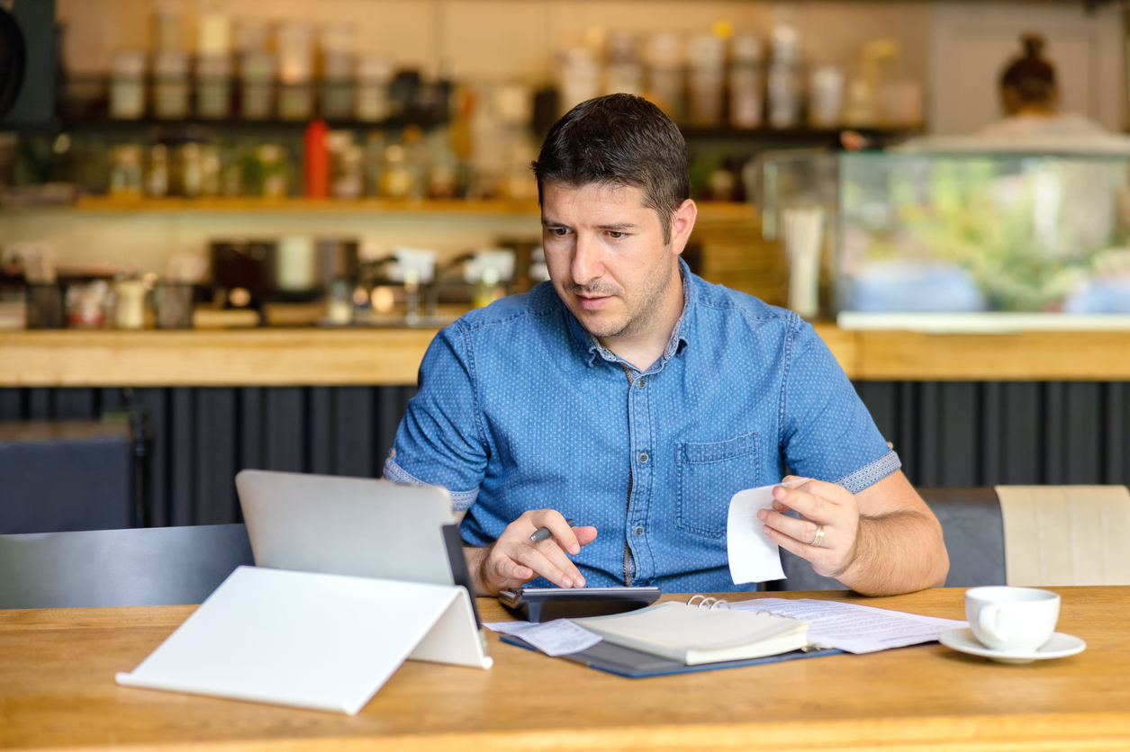 Coffee shop owner with bills, receipys and laptop working on taxes. Concept: Schedule C.
