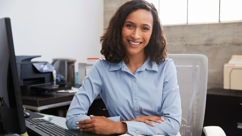 Young female professional at desk smiling to camera. concept: how to set up a budget
