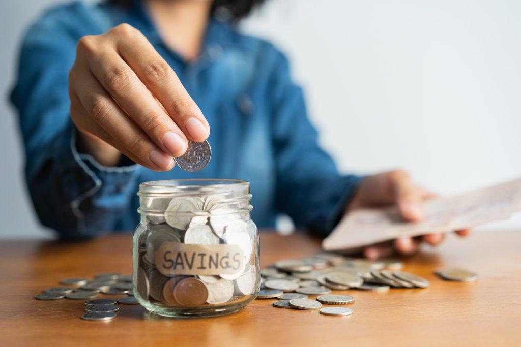 Mano poniendo dinero en un vaso con ahorros. concept: cuentas de ahorros