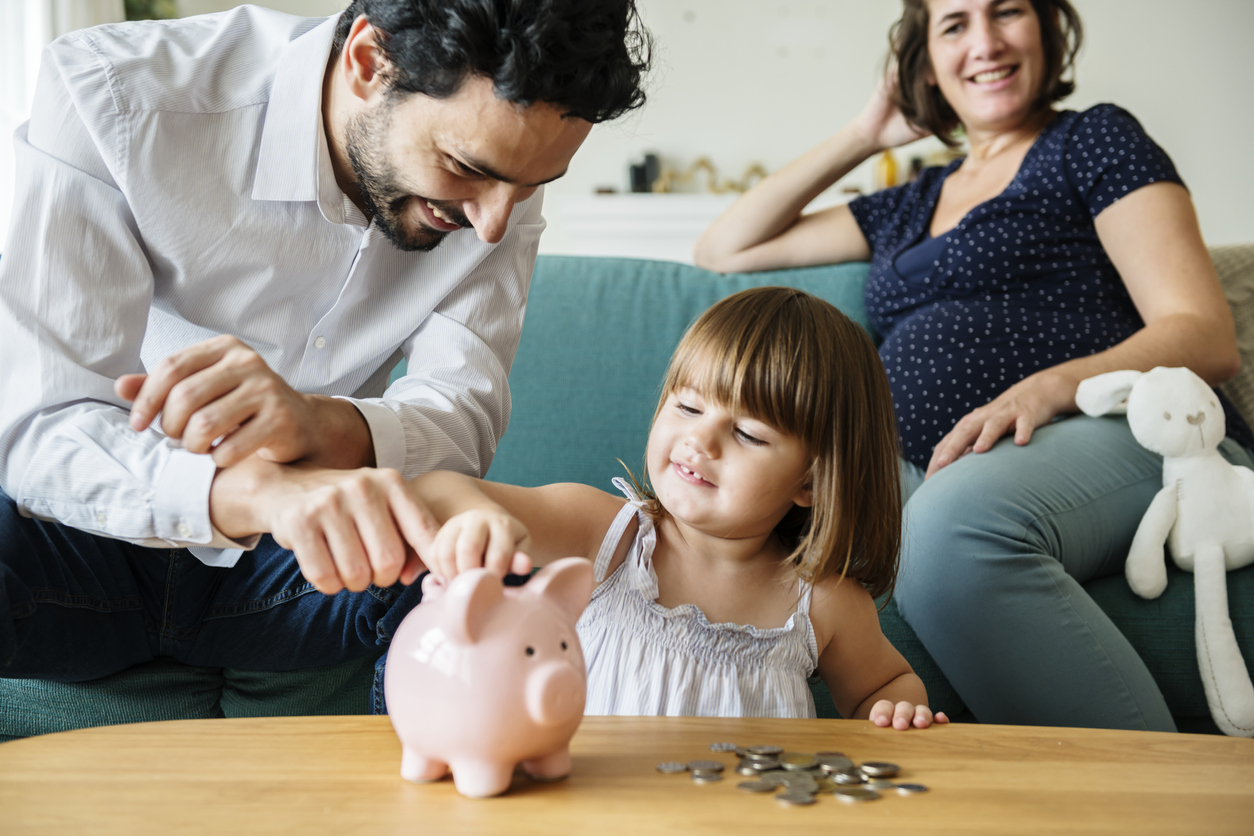 Family saving money in piggy bank. Concept: Types of business savings accounts