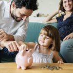 Familia en casa, la niña introduce dinero en una hucha de cerdito. Concepto: Tipos de cuentas de ahorros.