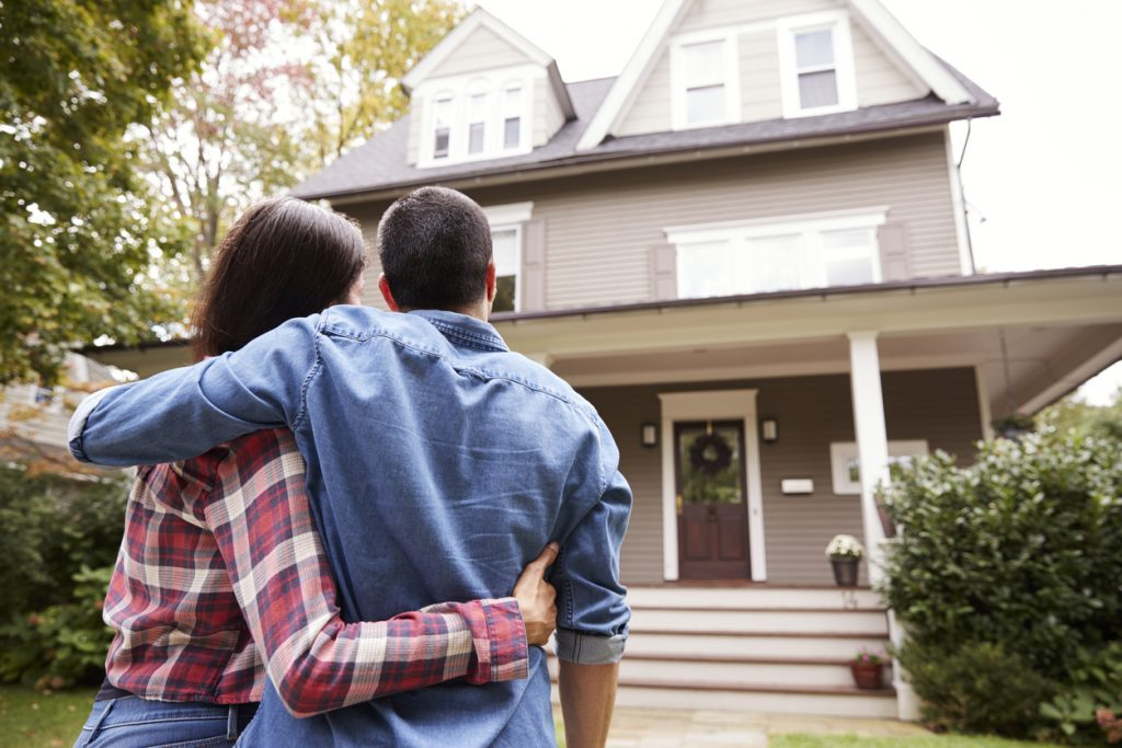 Rear View Of Loving Couple Looking At House. concept: Home Construction Loan