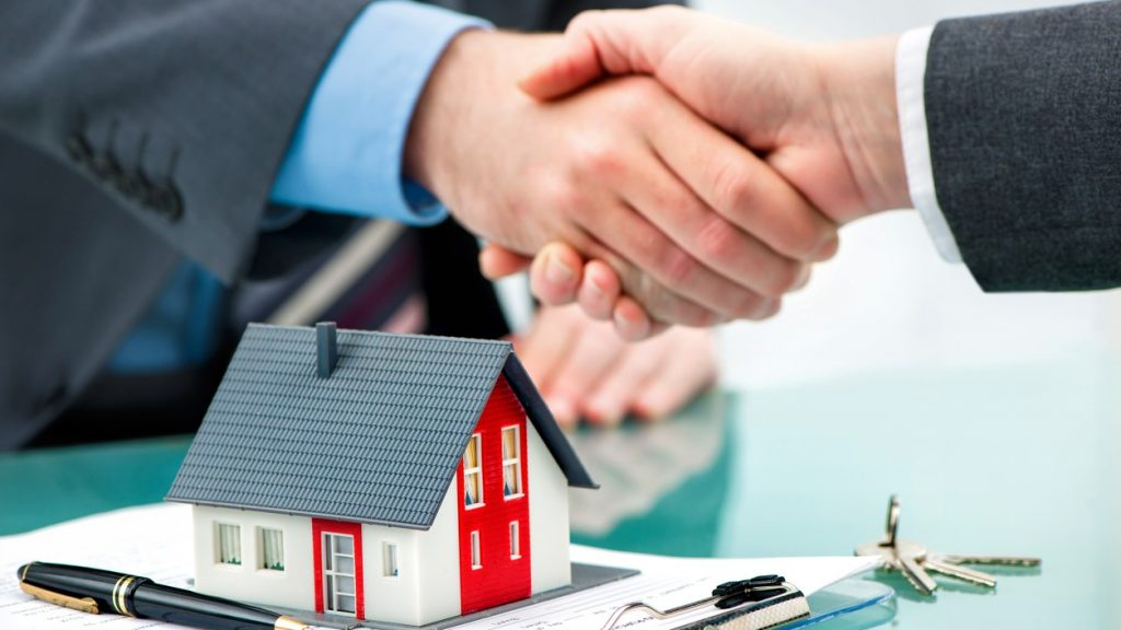 Estate agent shaking hands with customer after contract signature. concept: Home Construction Loan