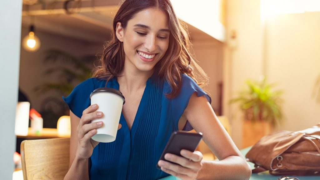 Young beautiful woman holding coffee paper cup and looking at smartphone while sitting at cafeteria. Happy university student using mobile phone. Businesswoman in casual clothes drinking coffee, smiling and using smartphone indoor. concept: finance apps
