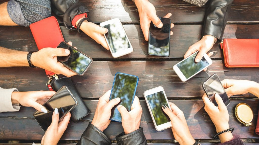 People group having addicted fun together using smartphones - Detail of hands sharing content on social network with mobile smart phones - Technology concept with millennials online with cellphones. concept: marketing to millennials