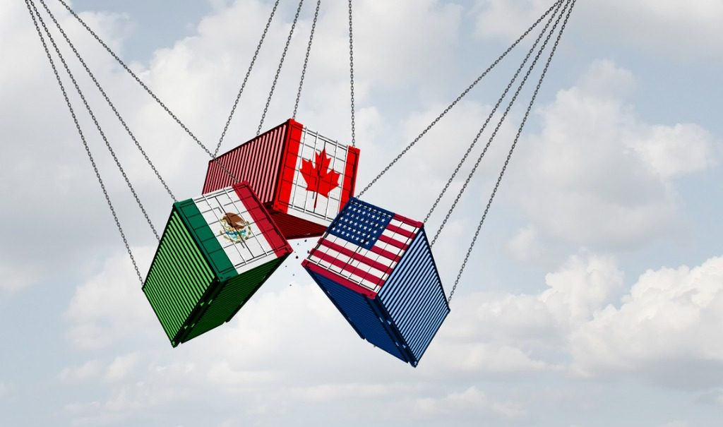 Three shipping containers with flags of Mexico, Canada and the US representing the USMCA.