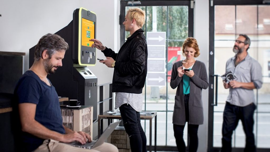 People stand at BITCOIN ATM and buy the cryptocurrencies. concept: best credit unions