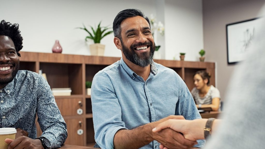 Two business people shaking hands while sitting in meeting room. Middle eastern businessman shake hands to businesswoman. Portrait of happy smiling latin man signing off deal with an handshake. concept: best credit unions