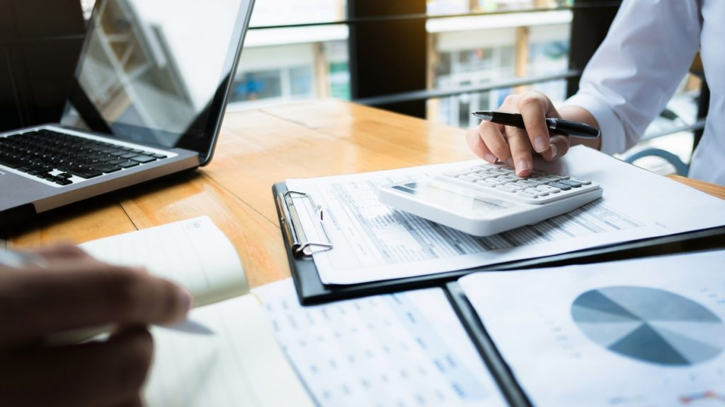 business audits using a calculator financial data investment fund at a workplace, wealth. concept: best payroll software