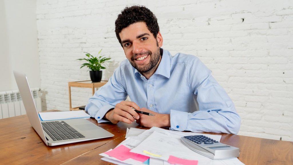 Happy attractive entrepreneur man calculating costs, charges, mortgage, taxes or paying bills with documents and laptop at home office. In online banking and Success business finances free of debts. concept: gross revenue