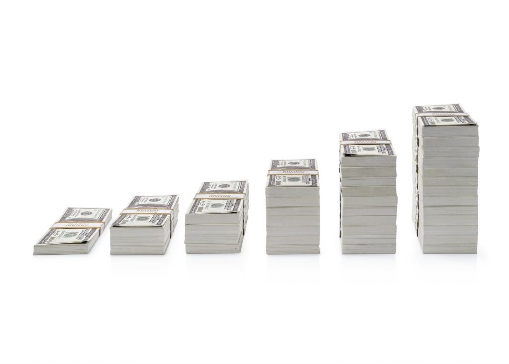 Increasing piles of dollar bills isolated on white background. concept: Compound Interest Accounts