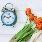 Clock next to bouquet of flowers. Concept: Daylight Saving Time
