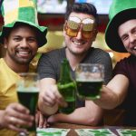 Three firends drinking green beer in a pub on St. Patrick's. Concept: restaurant marketing.
