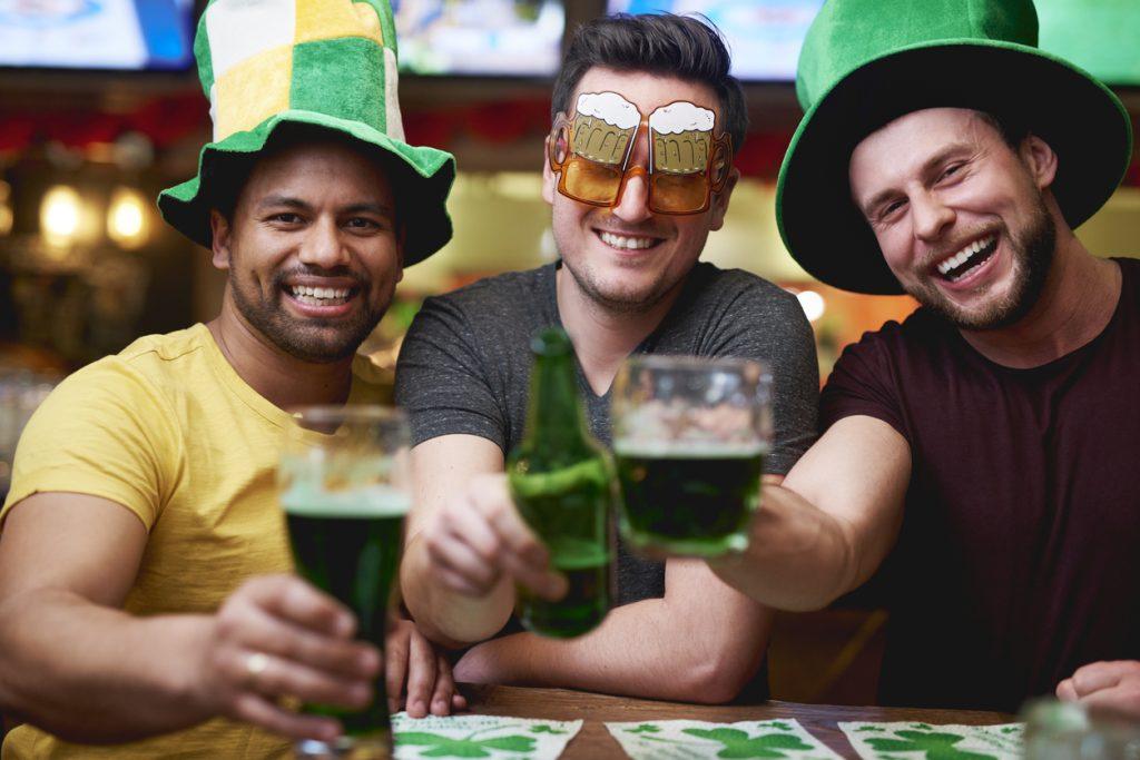 Tres amigos bebiendo cerveza verde en un pub el Día de St. Patrick.
