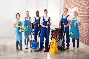 Portrait Of Happy Diverse Janitors In The Office With Cleaning Equipments. concept: cleaning company