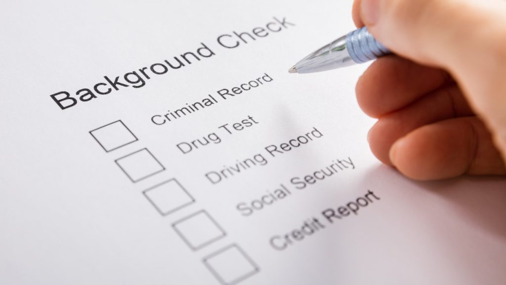 Close-up Of Person Hand Filling Background Check Form. concept: cleaning company