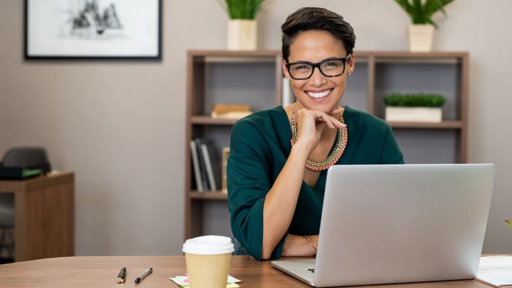 Portrait of happy casual businesswoman sitting at her desk in office. Cheerful latin woman working on laptop and looking at camera. Young fashionable girl wearing eyeglasses sitting at creative agency. concept: cleaning company
