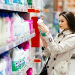 Woman selecting product in supermarket aisle. Concept: consumer rights.
