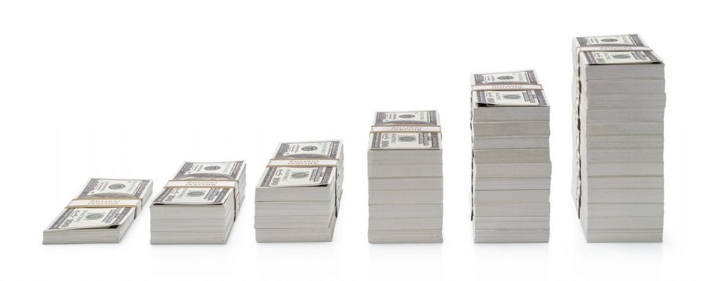 Increasing piles of dollar bills isolated on white background. concept: small businesses