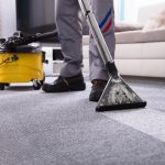 Low Section Of A Person Cleaning The Carpet With Vacuum Cleaner In Living Room. concept: Janitorial Services