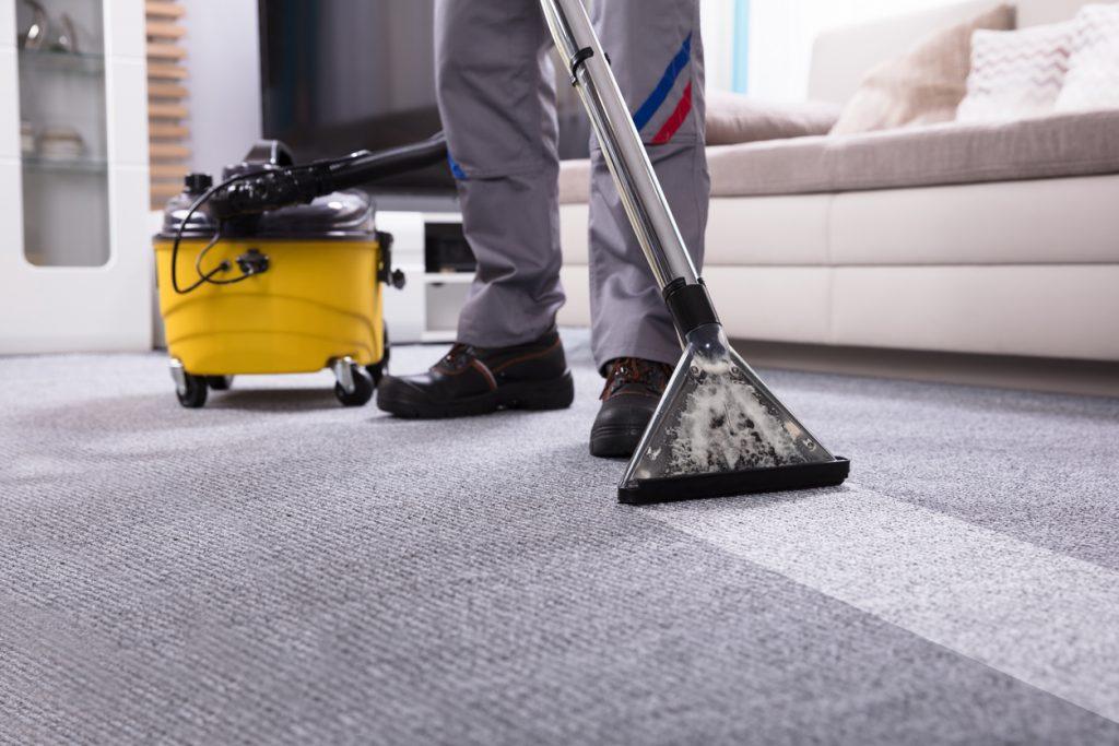 Persona limpiando alfombra con una aspiradora limpiadora. Concept: industria de limpieza