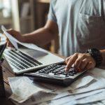Hombre usando calculadora y gesitonando sus cuentas por cobrar