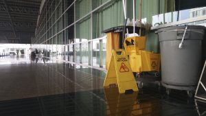 The warning signs cleaning and caution wet floor in the building and janitorial car parked in back to remind people to walk safely.