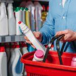 Vista parcial de persona colocando producto de limpieza en cesta de supermercado. Concepto: Cómo poner los precios duante una crisis