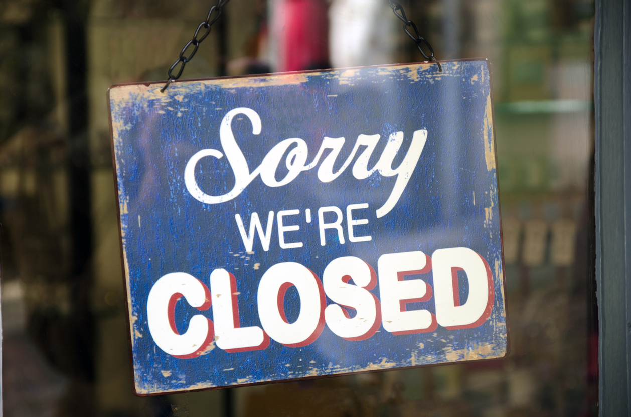 Old blue closed sign hanging in a shop window. Vintage closed sign in shop window. Concept: small businesses