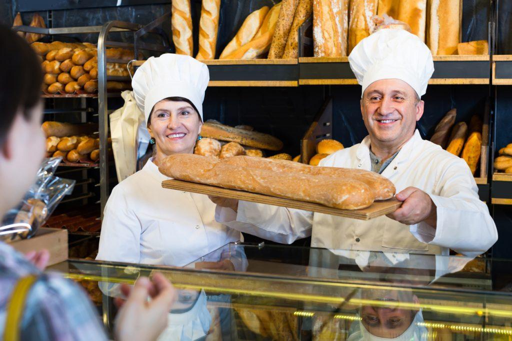 Dueños de panadería vendiendo pan fresco - negocio tradicional