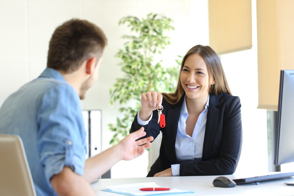 Happy real estate agent giving house keys to a customer after signing contract in the office. concept: renegotiate