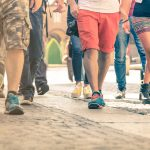 Crowd of people walking on the street - Detail of legs and shoes moving on sidewalk in city center - Travellers with multicolor clothes on vintage filter - Shallow depth of field with sunflare halo. concept: foot traffic