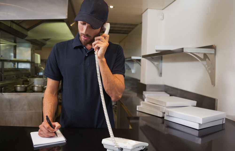 Pizza restaurant employee taking relivery rder over the telephone. Concept: Tips to keep your restaurant or bar in business during a health crisis