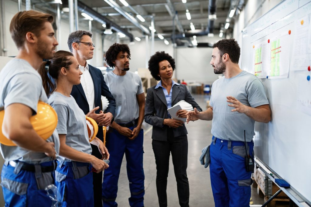Young factory worker holding presentation about production development to company managers and his coworkers. concept: business continuity plan