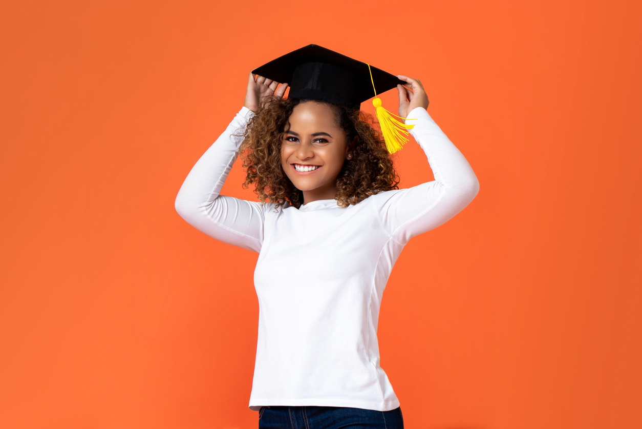 Happy smiling young African American woman wearing graduation cap isolated on orange background for education concepts, camino financial