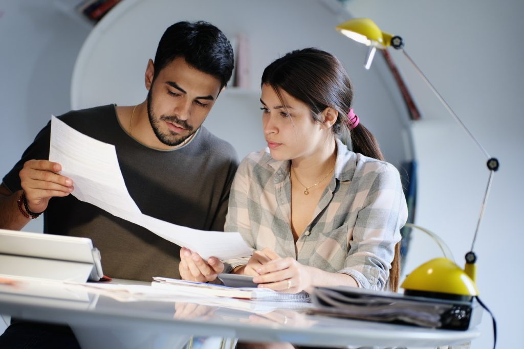 Young couple reviewing invoices and doing family business plan. Concept of money and economic problem for man and woman living together. concept: coronavirus stimulus
