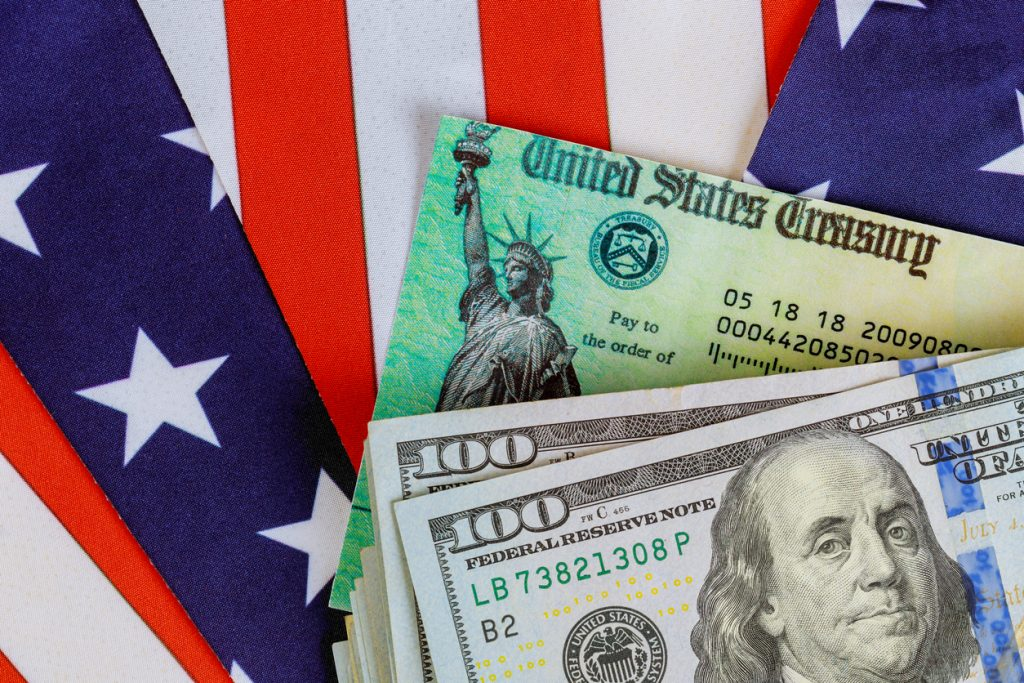 USA dollar cash banknote stimulus economic tax return check with US flag. concept: COVID-19 Stimulus Check
